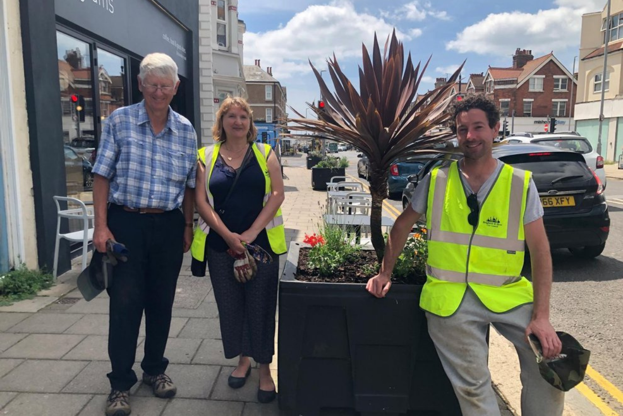 TV gardener helps volunteers revive planters in shopping street. Published by Brighton and Hove Independent.